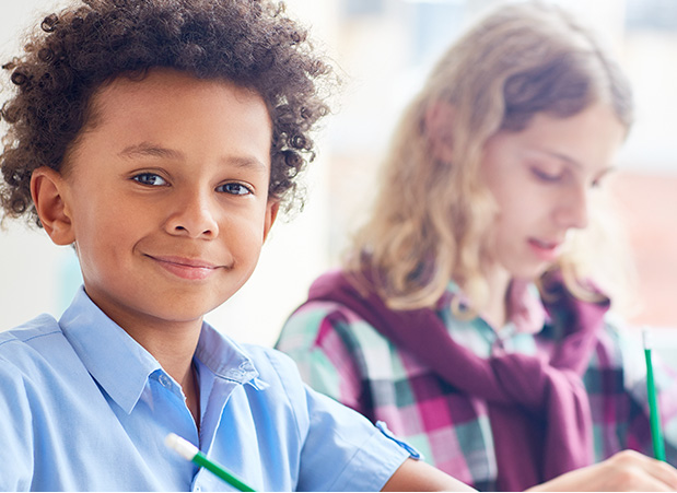 Uma criança negra olha para frente e uma criança branca olha para baixo